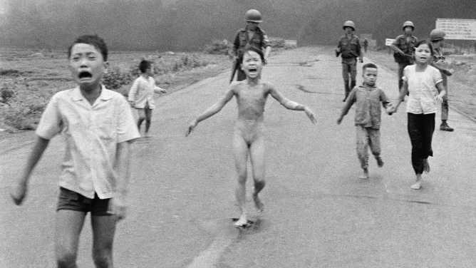 South Vietnamese forces follow after terrified children, including 9-year-old Kim Phuc, center, as they run down Route 1 near Trang Bang after an aerial napalm attack, June 8, 1972.
