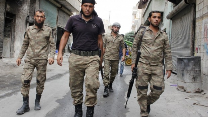 """Members of the """"Liwaa al-Sultan Mrad"""" brigade, operating under the Free Syrian Army, walk along a street in Aleppo's Bustan al-Basha district on September 19, 2013. (Photo: REUTERS - Molhem Barakat)"""