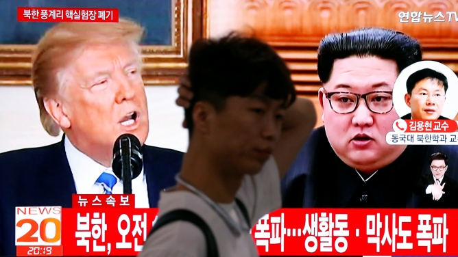 A man walks past a TV showing US President Donald Trump and North Korean leader Kim Jong-un, in Seoul, May 24, 2018.