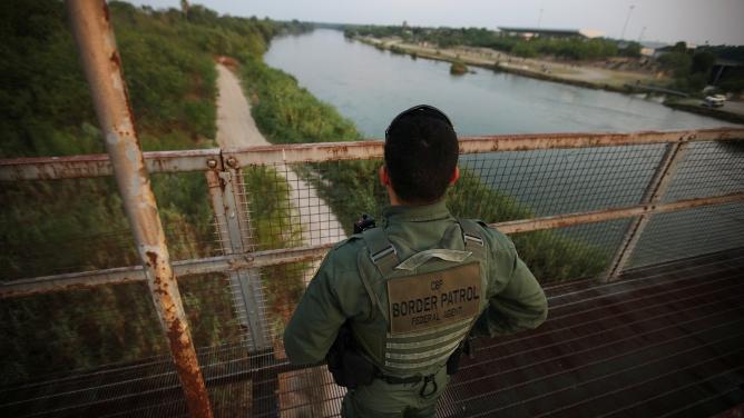 Agent in uniform stands on bridge looking over green river