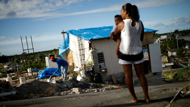 Samuel Vasquez rebuilds his house, which was partially destroyed by Hurricane Maria, while his wife, Ysamar Figueroa, looks on in Canovanas, Puerto Rico, Dec. 11, 2017. Puerto Rico is once again bracing for hurricane season, just as a new study has found