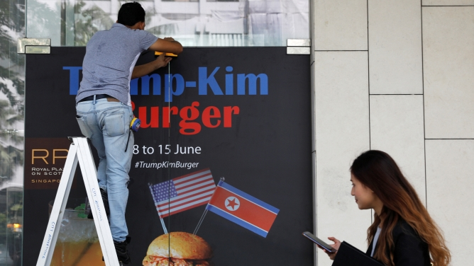 A worker in blue jeans, stands on a ladder and puts up an advertisement for the Trump-Kim burger.