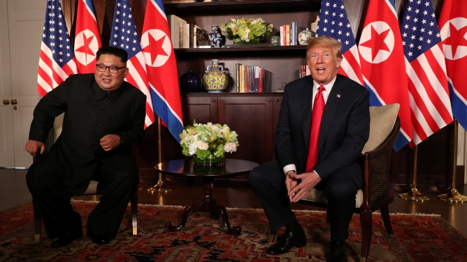 US President Donald Trump sits next to North Korea's leader Kim Jong-un with the flags of both countries behind them.