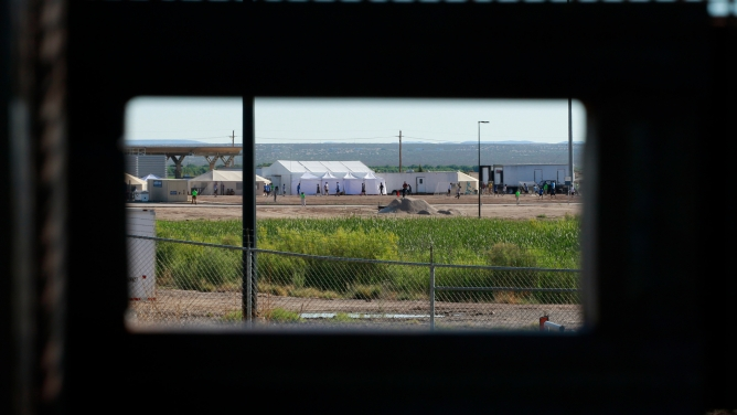 In the distance children of detained migrants are seen play soccer at a tent encampment near the US Customs and Border Protection port of entry in Tornillo, Texas.