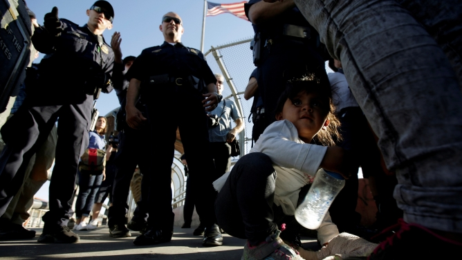 A you migrant girl crouches next to her family as they listen to officers of the US Customs and Border Protection before entering the United States to apply for asylum.