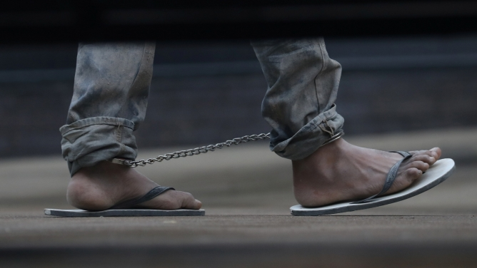 An undocumented immigrant is shown in shackles in a picture taken on the other side of a vehicle from underneath, just showing the feet.