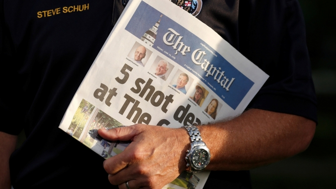 In this close-up photograph, County Executive Steve Schuh holds a copy of the Capital Gazette.