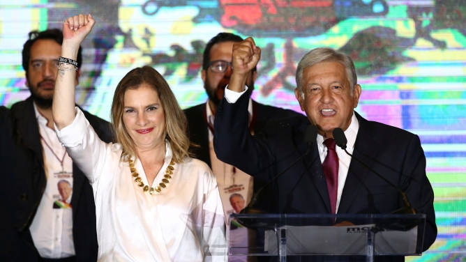 Andrés Manuel López Obrador and his wife Beatriz Gutierrez Muller raise their clenched hands on a stage in Mexico City.