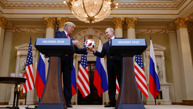 US President Donald Trump is handed a soccer ball from Russia's President Vladimir Putin while the two men stand behind podiums.