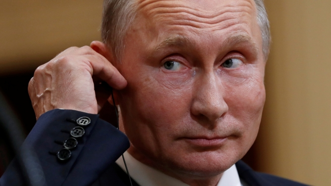 A close-up photography of Russian President Vladimir Putin touching an ear piece.