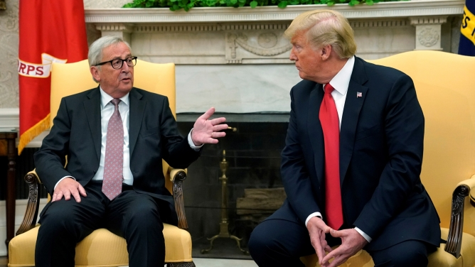 US President Donald Trump sits on the edge of an armchair next to European Commission President Jean-Claude Juncker who is also seated.