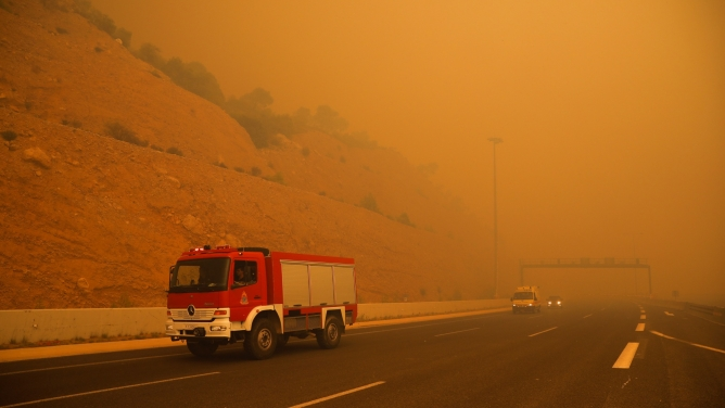 A fire truck drives along a road in Greece amid orange smoke.