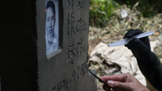 Tony and Daniel Luu etch their father's tombstone on the Indonesian island of Kuku.