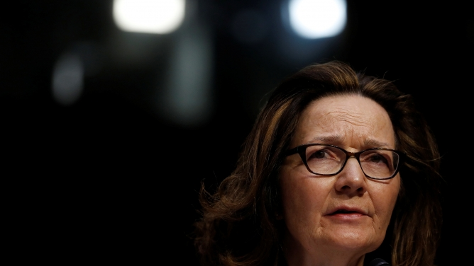 CIA Director Gina Haspel, wearing dark rimmed glasses, looks right in the medium cropped portrait.