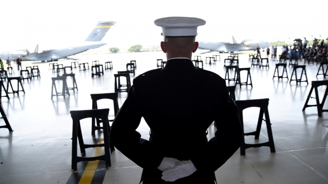 A US Marine is shown from behind standing at attention in full uniform as caskets containing the remains of American servicemen from the Korean War.