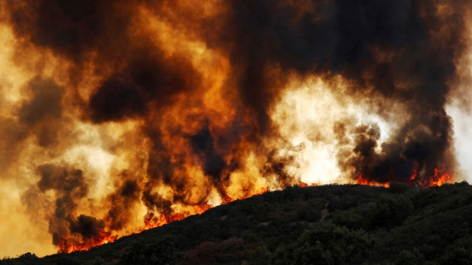 Wind-driven flames roll over a forested hill toward homes during near Lakeport, California, August 2, 2018.