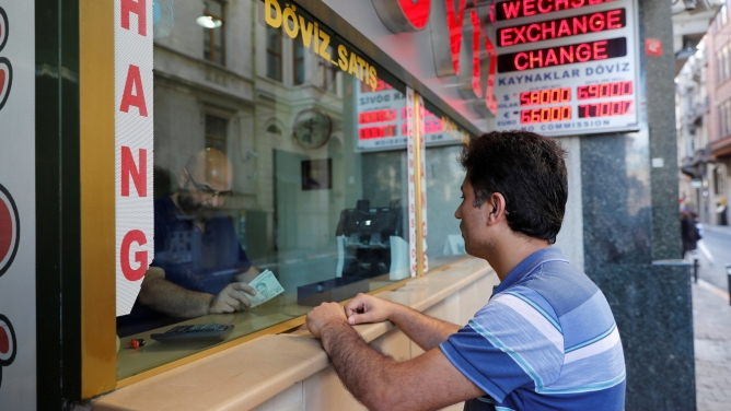 A man leans on the counter to change money at a currency exchange office in Istanbul, Turkey August 13, 2018.