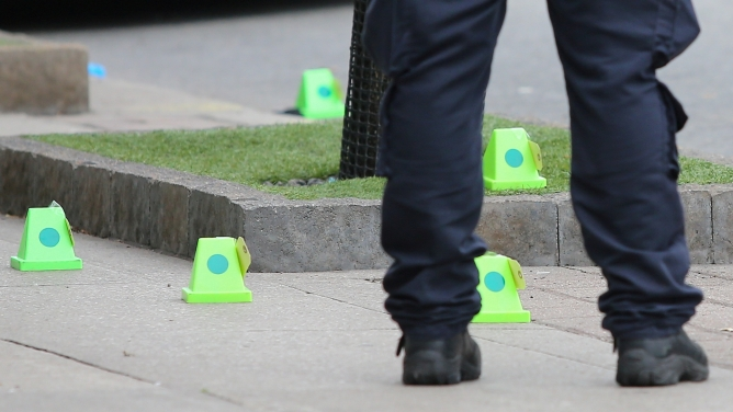 A police officer stands near evidence markers while investigating a mass shooting on Danforth Avenue in Toronto, Canada.