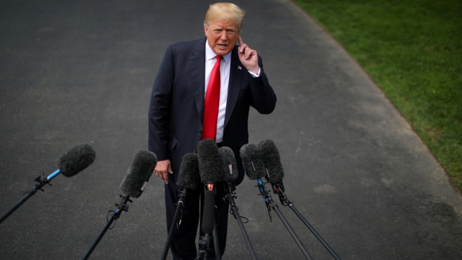 President Donald Trump is shown with his hand cupping his ear in front of several microphones outside.