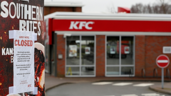 A paper sign is taped on top of a KFC ad telling customers that the restaurant is closed.