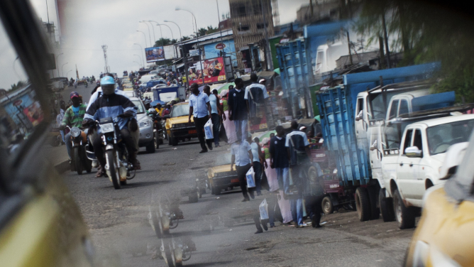 A reflection from the wing mirror of a car shows people ride motorcycles in Douala.