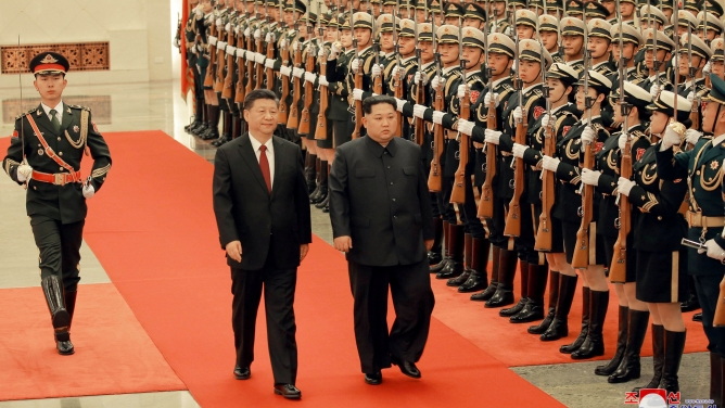 North Korean leader Kim Jong-un and Chinese President Xi Jinping walk past an rifle-clad honor guard.
