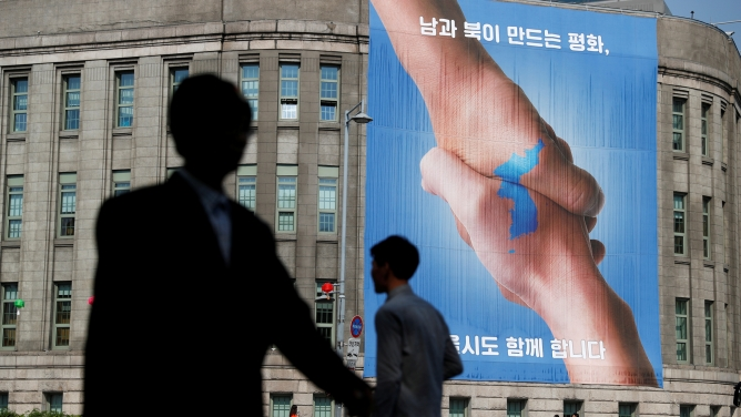 People walk past a large banner adorning the exterior of City Hall ahead of the upcoming summit between North and South Korea in Seoul.