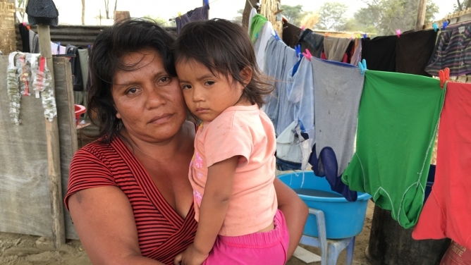 Flor Bautista holds her daughter Camila in her arms, both looking directly at camera.