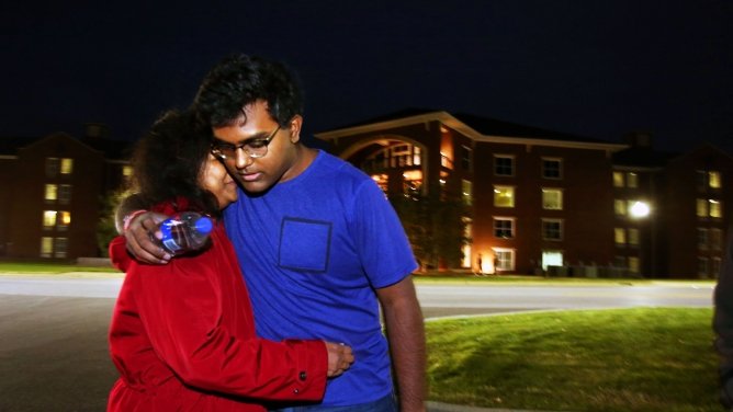 Woman hugs man in evening scene in front of building