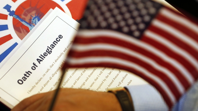The Oath of Allegiance is held next to an American flag during a naturalization ceremony for citizen candidates in Washington, DC, on July 3, 2013.