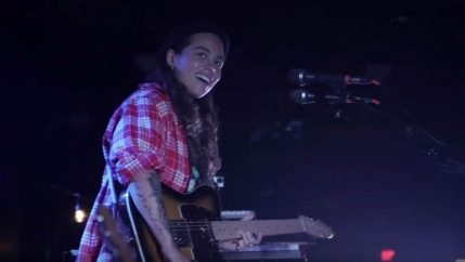 Tash Sultana is seen smiling on stage at the Paradise Rock Club in Boston.