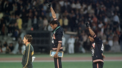 three men stand on podiums, two with their fists in the air
