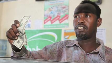 A customer receives USnotes from a teller at the Dahabshill money transfer office in Mogadishu, Somalia, Feb.16, 2015.