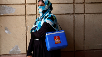 A woman wearing a scarf over her face stands by a wall carrying a polio vaccination kit box in Pakistan