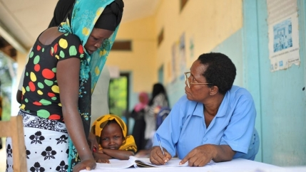 A young Tanzanian woman speaks to a male doctor.