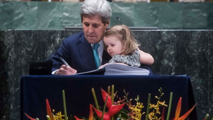John Kerry signs Paris Climate Agreement holding granddaughter