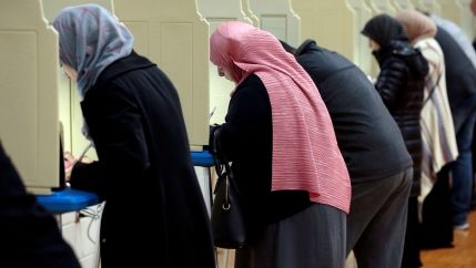 Women wearing headscarves cast ballots in a line of voting booths.