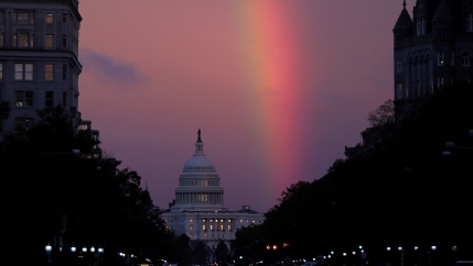 A rainbow stretches across the sky above the US Capitol dome