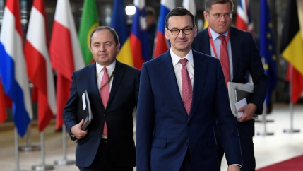 Three men in suits walking in front of flags
