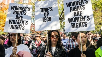 Three female Google workers hold protest signs with black lettering.