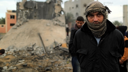 A Palestinian man wears a scarf and looks on as he stands in front of a building that was destroyed by an Israeli air strike.