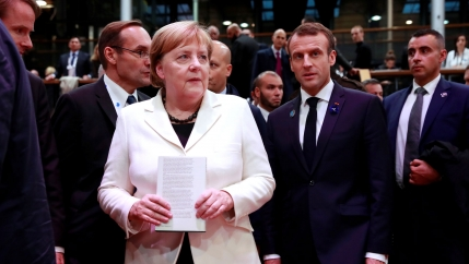 German Chancellor Angela Merkel, wearing a white jacket, and French President Emmanuel Macron, in a dark suit, are shown standing next to each other at the Paris Peace Forum.