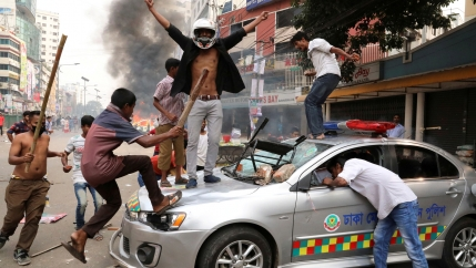 Five young Bangladesh Nationalist Party activists vandalize a police vehicle with batons