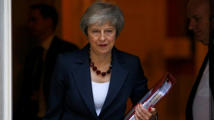 Theresa May is shown with a folder in her left hand walking out of 10 Downing Street, in London.