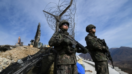 South Korean soldiers stand guard as construction equipment destroys a guard post in the Demilitarized Zone dividing the two Koreas in Cheorwon, Nov. 15, 2018.