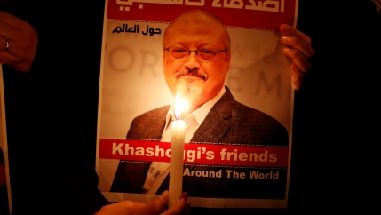 Poster with a picture of Saudi journalist Jamal Khashoggi lit up by candelight.