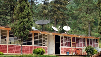 Satellites on the roof of a red brick school in Oaxaca state surrounded by green trees.
