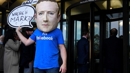 A campaigner from a political pressure group wears an oversized mask of founder and CEO of Facebook Mark Zuckerberg