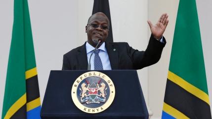 Tanzanian President John Magufuli waves at a podium.