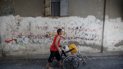 Gaza boy pushing wheelchair water